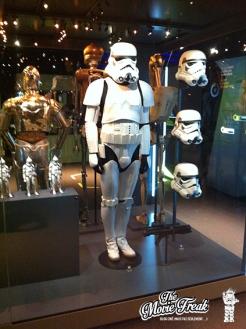 Un costume de Stormtrooper, à côté de 3 casques utilisés sur les épisodes IV, V et VI.